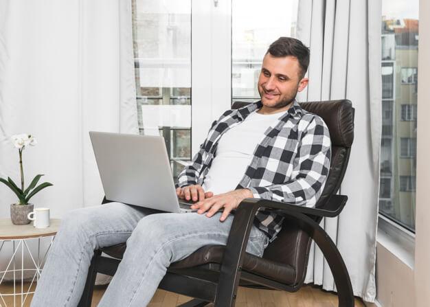 Hombre trabaja cómodo en sillón de oficina en casa